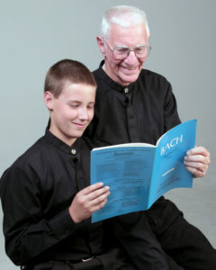 Two people sitting together reading music