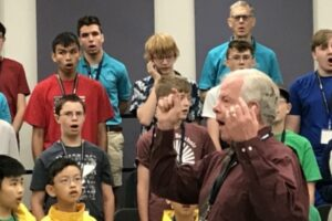 Dr. Ackerley conducting while boys sing in background
